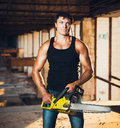 Muscular man with a chainsaw on the ruins Royalty Free Stock Photography