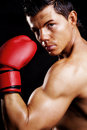 Muscular man fighting box over dark Royalty Free Stock Image