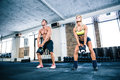 Muscular man and fit woman lifting kettle ball Royalty Free Stock Photo