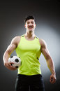 The muscular man with football ball Royalty Free Stock Photo