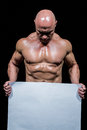 Muscular man holding blank paper Royalty Free Stock Photo