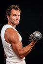 Muscular man lifting dumbbell Stock Photography