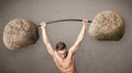 Muscular man lifting large rock stone weights strong Royalty Free Stock Photography