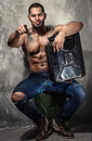 Muscular man with metal fuel can indoors Stock Images