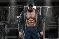 Muscular man with open jacket revealing chest and abs in gym, workout