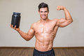 Muscular man posing with nutritional supplement in gym portrait of a Royalty Free Stock Photo