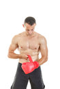 Muscular man putting his boxing gloves preparing for training o fit in front of camera over white background Stock Images