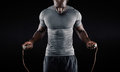 Muscular man skipping rope portrait of young exercising with jumping on black background Royalty Free Stock Image