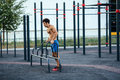 Muscular man warming up before exercise at crossfit ground doing push ups as part of training. Sport concept Royalty Free Stock Photo