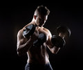 Muscular man weightlifting attractive on dark background Royalty Free Stock Photos