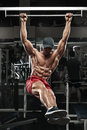 Muscular man working out in gym, doing stomach exercises on a horizontal bar, strong male naked torso abs Royalty Free Stock Photo
