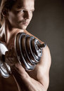 Muscular man young with dumbbells on black background Royalty Free Stock Photos