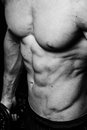 Muscular sexy torso of young sporty man with perfect abs close up. Black and white isolated on black background Royalty Free Stock Photo