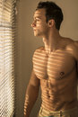 Muscular shirtless man next to venetian blinds lit by sun behind looking out of the window sad Stock Photo
