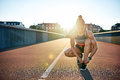 Muscular woman ties her running shoes on bridge Royalty Free Stock Photo