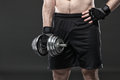 Muscular yong man exercising with dumbbell Royalty Free Stock Photo
