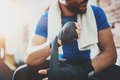 Muscular young boxer with black boxing bandages. Fists of fighter before the fight or training in sport gym. Blurred