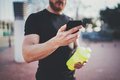 Muscular young man checking burned calories on smartphone application after good workout outdoor session on sunny park Royalty Free Stock Photo