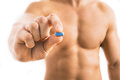 Muscular young man holding blue pill Royalty Free Stock Photo