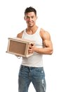 Muscular young man holding parcel over white background Royalty Free Stock Photography
