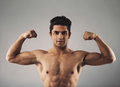 Muscular young man showing off his defined body portrait of macho and pulling bicep to show hispanic flexing biceps isolated on Stock Photos