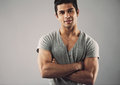 Muscular young man standing with his arms crossed cropped image of against grey background macho posing confidently Stock Photography
