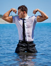 Muscular young sexy guy standing in the sea in business suit wet is pants a shirt and tie Royalty Free Stock Photos