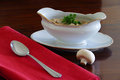 Mushroom cream soup in a gravy boat, red fabric, dark brown wood Royalty Free Stock Photo