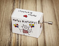 Music box with funny title happy birthday on the wooden background Stock Photos
