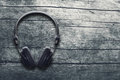 Music grunge background, black headphones on a wooden table Royalty Free Stock Photo