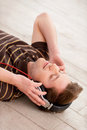 Music i my life top view of handsome young man in headphones listening to the and keeping eyes closed while lying on the floor Royalty Free Stock Photos