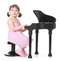 Music in my heart little girl playing on a miniature piano Royalty Free Stock Photo