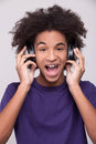 Music is my life cheerful african teenager in headphones listening to the and expressing positivity while standing isolated on Stock Photos