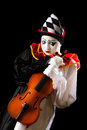 Music pierrot musical holding an old violin against a black background Stock Image