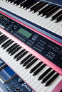 Music synthesizer keyboards on rack  Stock Images