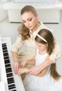 Music teacher teaches little girl to play piano tutor concept of study and leisure Stock Photography