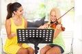 Music teacher tutoring beautiful young girl to play violin Stock Photography