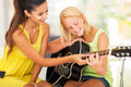 Music teacher tutoring smiling beautiful young girl to play guitar Stock Image
