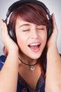 Musica d'ascolto della donna teenager alle cuffie Fotografia Stock