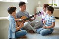 Musical family portrait of handsome siblings and their father playing instruments at home Royalty Free Stock Image