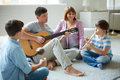 Musical family portrait of handsome siblings and their father playing instruments at home Royalty Free Stock Images