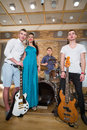 Musical group of three guys and one girl are standing Royalty Free Stock Photo