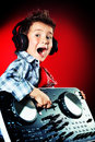 Musical hobby expressive little boy dj in headphones mixing up some party music Royalty Free Stock Image