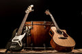 musical instruments, bass drum barrel acoustic guitar and bass guitar on a black background Royalty Free Stock Photo
