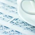 Musical notation and a white coffee cup Stock Photo