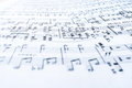 Musical notes on wavy white sheet of paper. Selective focus.
