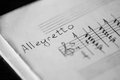 Musical tempo allegretto in a music book with hand written notes black and white Royalty Free Stock Photo