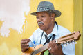 Musician playing traditional music in havana cuba – february street cuban on an acoustic guitar for the entertainment of Royalty Free Stock Photography