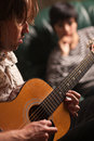 Musician Plays His Guitar as Friend Listens Royalty Free Stock Images