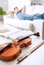 Musician relaxing at home violin close up with man and listening to music on background Stock Photography